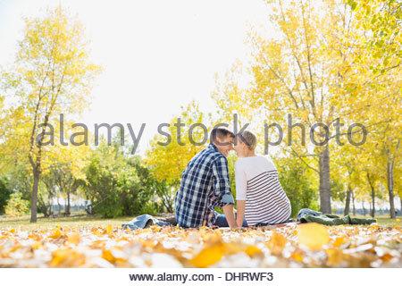 Romantic couple sitting in park - Stock Photo