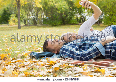 Cheerful couple taking self portrait while lying in park - Stock Photo