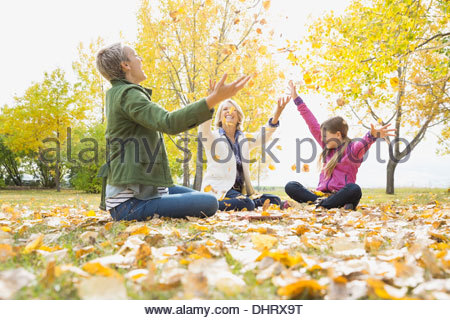 Female family members throwing autumn leaves in park - Stock Photo