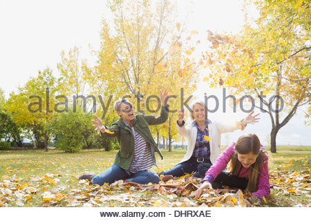 Three generation females playing with autumn leaves in park - Stock Photo