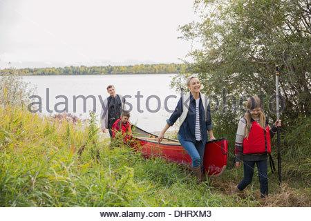 Family carrying canoe by lakeshore - Stock Photo
