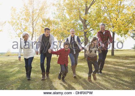 Cheerful multi-generation family running in park - Stock Photo