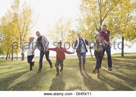 Multi-generation family running in park - Stock Photo