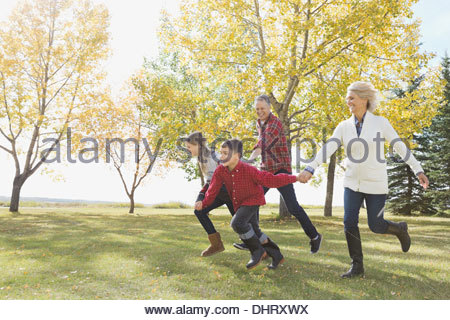 Happy children running with grandparents outdoors - Stock Photo