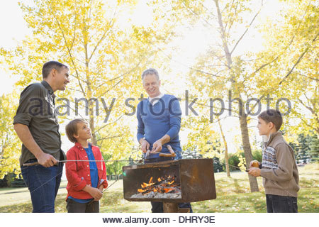 Male family members cooking hot dogs in park - Stock Photo