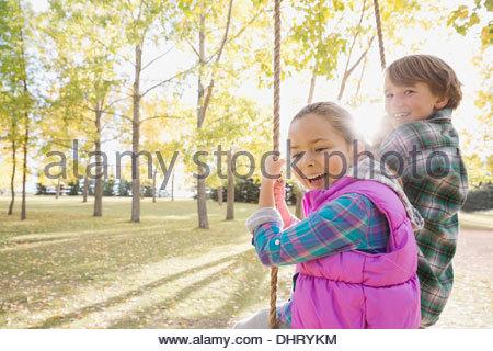 Siblings swinging at park - Stock Photo