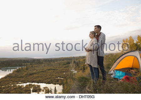 Loving embracing woman from behind at campsite - Stock Photo