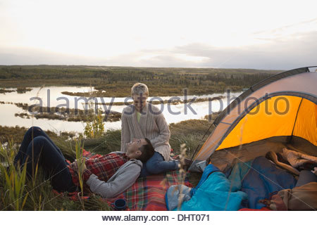 Man resting on womans lap at campsite - Stock Photo