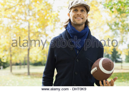 Man with American football at park - Stock Photo