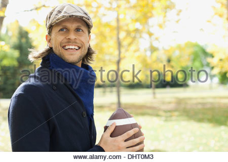 Happy mid adult man playing American football at park - Stock Photo