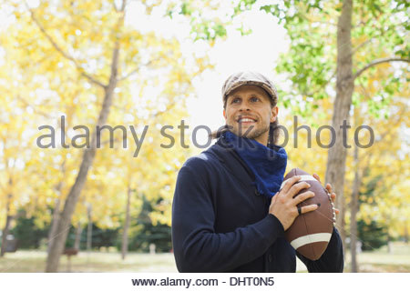 Smiling man playing American football at park - Stock Photo