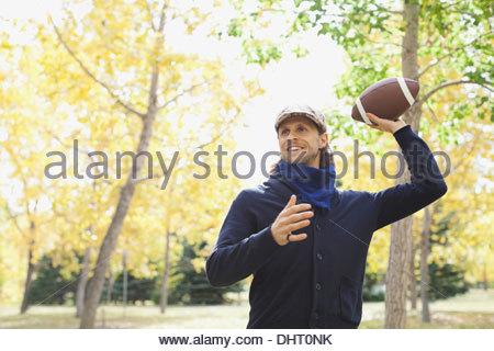 Man playing American football at park - Stock Photo