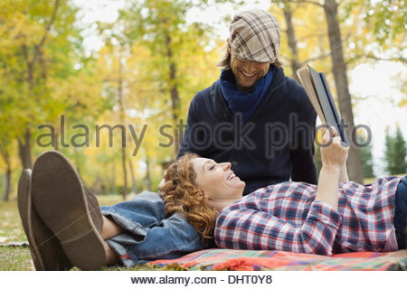 Happy woman reading book while resting on mans lap at park - Stock Photo