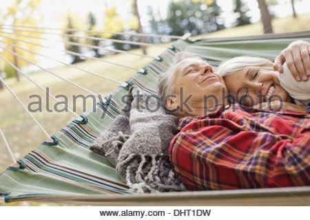 Loving mature couple lying in hammock at park - Stock Photo