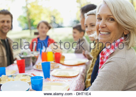 Portrait of happy mature woman with family at dining table in park - Stock Photo