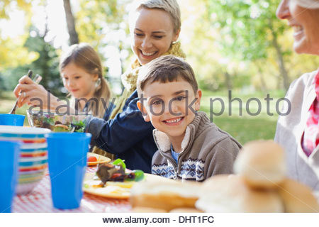 Portrait of happy boy with family at dining table in park - Stock Photo
