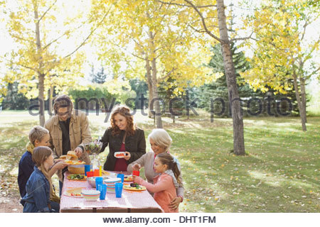 Multi-generation family enjoying meal in park during autumn - Stock Photo