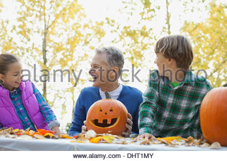 Happy grandfather and boy with jack o lanterns looking at girl in park - Stock Photo