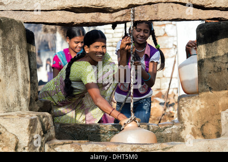 Indian woman and teenage girls drawing water from a well in a rural Indian village street. Andhra Pradesh, India - Stock Photo