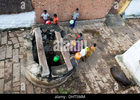 Indian women, men and children drawing water from a well in a rural Indian village street. Andhra Pradesh, India - Stock Photo