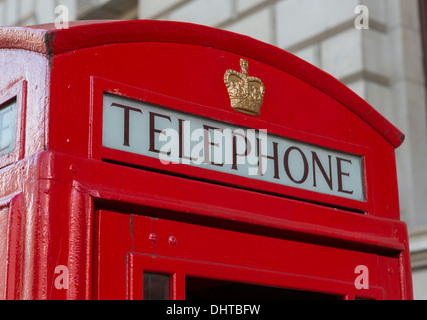 Sign on a classic red telephone booth in London, England - Stock Photo