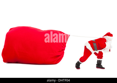 Santa claus carrying a heavy gift sack - Stock Photo