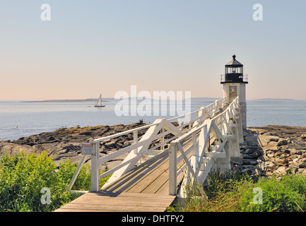 Marshall Point Lighthouse with view of Penobscot Bay and sailboat, St.George Peninsula, Port Clyde Maine USA - Stock Photo