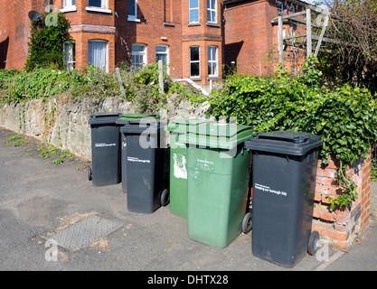 Black (general) and green (recycling) rubbish bins on the pavement in Maidstone, England. - Stock Photo