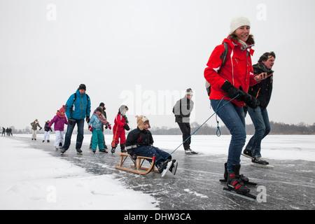 Netherlands, Loosdrecht, Lakes called Loosdrechtse Plassen. Winter. Family ice skating with sledge - Stock Photo
