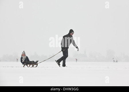 Netherlands, Loosdrecht, Lakes called Loosdrechtse Plassen. Winter. Father ice skating with son on sledge - Stock Photo