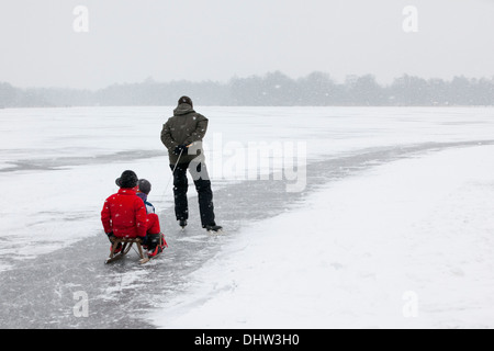 Netherlands, Loosdrecht, Lakes called Loosdrechtse Plassen. Winter. Father ice skating with sons on sledge - Stock Photo