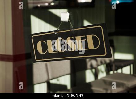 Closed sign hanging on shop door England UK United Kingdom GB Great Britain - Stock Photo