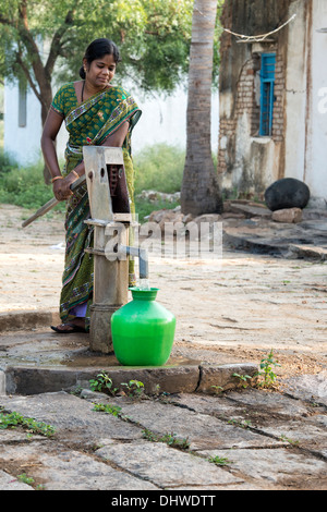 Indian woman filling plastic water pot from a rural village hand pump. Andhra Pradesh, India - Stock Photo