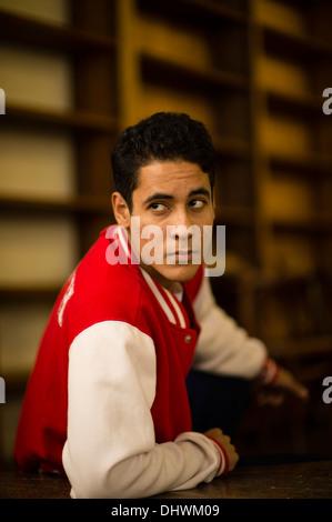 A young hispanic man male wearing an baseball jacket indoors uk - Stock Photo