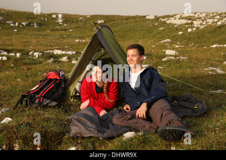 A young couple is watching the sunset while camping in the mountains - Stock Photo