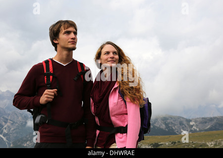 Young couple looking up in the mountains and enjoying freedom - Stock Photo