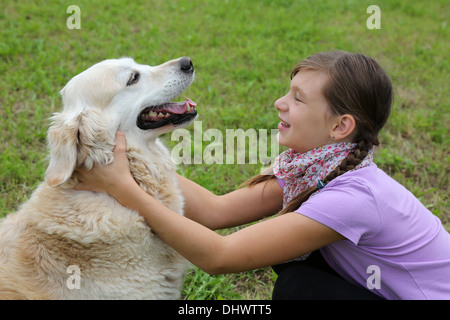 Little girl playing with a dog on a meadow - Stock Photo