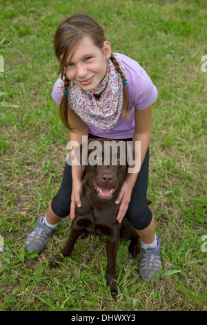 Little girl embracing her dog friend on a meadow - Stock Photo