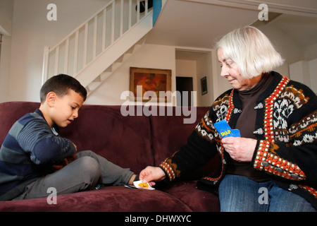 7-year-old boy playing cards with his grandmother - Stock Photo