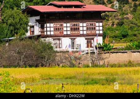 Typical Farmhouse Surrounded by rice paddies,containing animals on First Floor,Inhabitants on second floor,Paro,Bhutan - Stock Photo