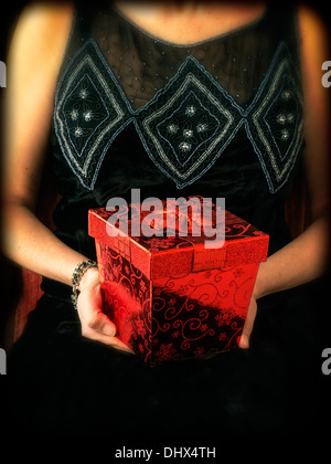 A cropped woman in a period dress holding a fancy red gift box - Stock Photo