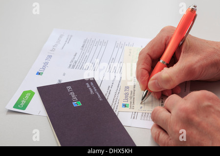 Senior woman pensioner writing a Lloyds TSB bank cheque to pay a large credit card bill. Wales, UK, Britain - Stock Photo