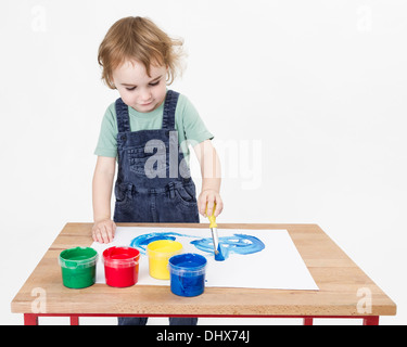 cute girl painting on small desk in grey background. studio shot - Stock Photo