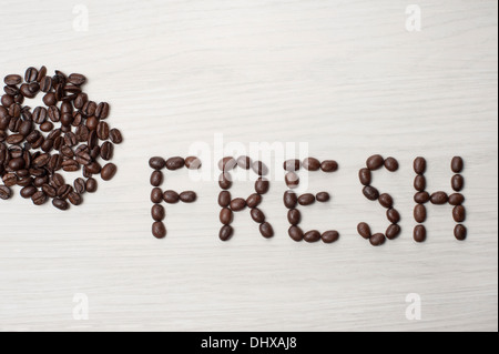 coffee beans used to spell out the word fresh on a white wood grain background with a scattering of coffee beans - Stock Photo