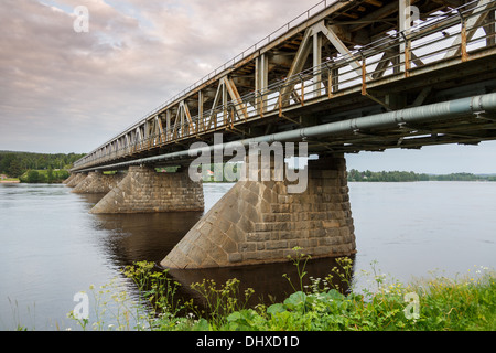 The old post-WW2 double-deck bridge across the Kemijoki river in the city of Rovaniemi by the Arctic Circle. - Stock Photo