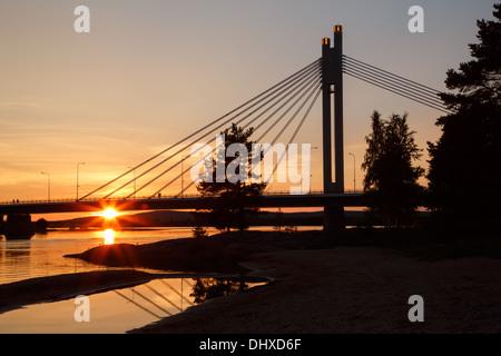 Midnight sun shining on Jätkänkynttilä (Lumberjack's Candle) bridge over the Kemijoki river in Rovaniemi by the - Stock Photo