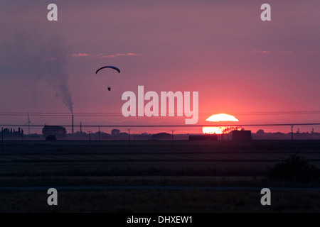 Paraglider flying above the fen landscape at sunset. - Stock Photo