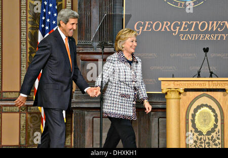 US Secretary of State John Kerry holds hands with Former Secretary of State Hillary Clinton as they walk on stage - Stock Photo