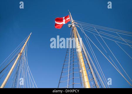 Mast and Danish flag on a large sailing ship in Amaliehaven in Copenhagen, Denmark - Stock Photo