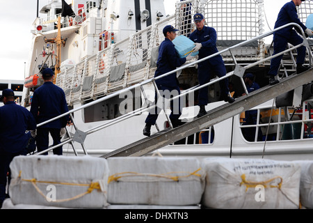Crew members aboard the Coast Guard Cutter Vigorous form a line down the cutters brow, transferring bales of contraband - Stock Photo